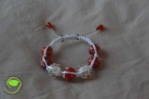 Bracelet de type Shamballa avec des perles de tailles différentes mais assez grosses de couleurs orange, blanche et nacré noir avec une queue de rat blanche