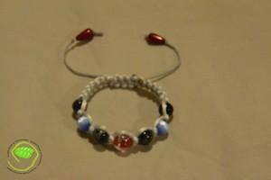 Bracelet de type Shamballa avec des perles de petites dimensions de couleurs rouge, noir, marron et bleu avec une queue de rat gris claire