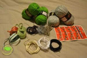Laine verte et grise, pressions à coudre, queues de rat (noir, blanche et beige), fils en cuir (noir, violet, gris et beige), biais vert, et deux rubans