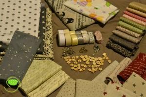 Pleins de tissus de toutes sortes essentiellement en coupons en lin et en coton, des chevrons, du biais, des charms, des crochets et des boutons en bois. Il y avait aussi deux boutons de Manucréa que j'ai oublié sur la photo.