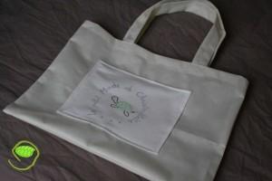 En tissu non tissé écru avec un appliqué en coton sur lequel j'ai dessiné à la peinture textile mon petit logo