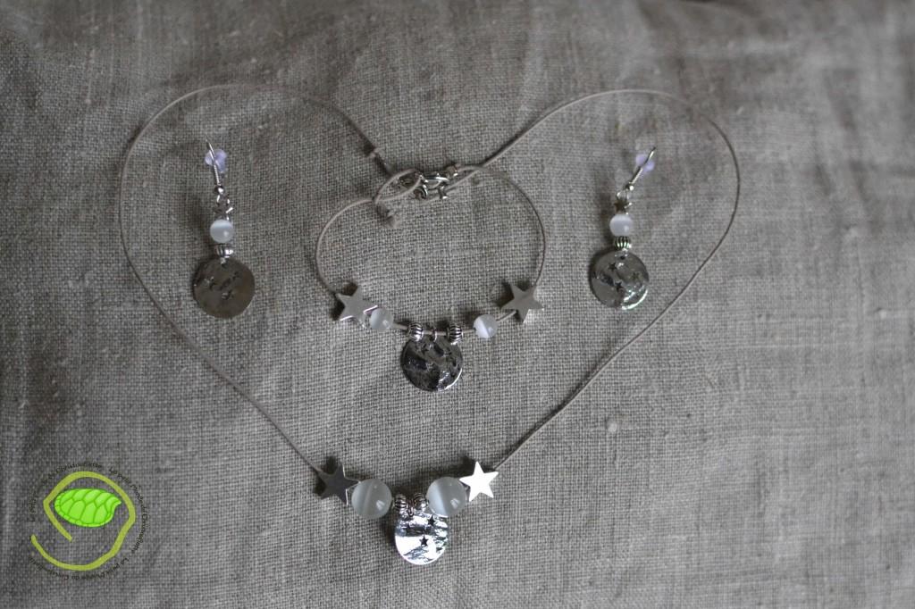 """Ensemble boucles d'oreilles, bracelet et collier avec des perles """"oeil de chat"""" blanches, un cordon en cuir beige et les fameuses médailles à étoiles"""