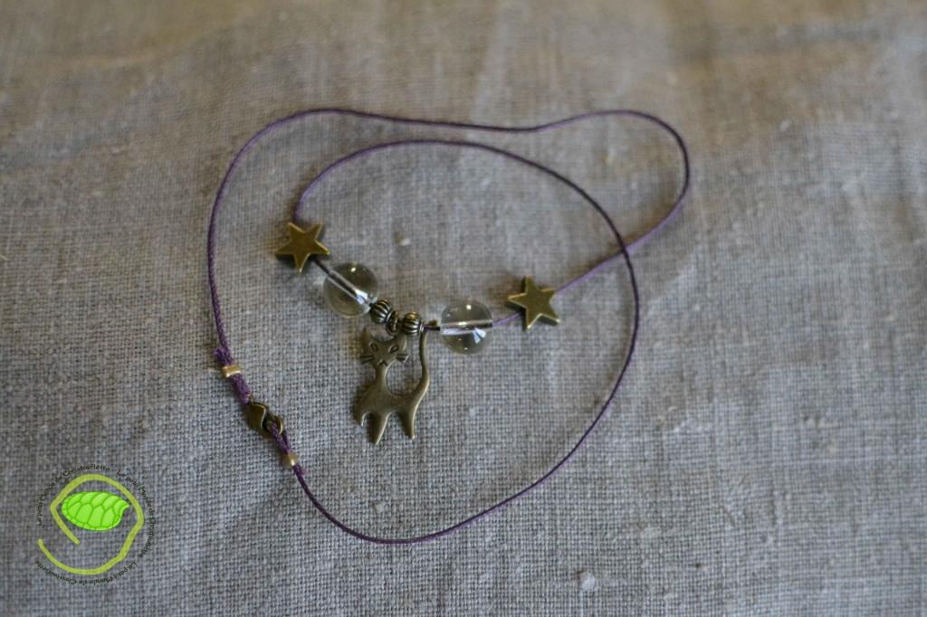 De couleur bronze avec des perles transparentes, une cordelette violette et un petit chat