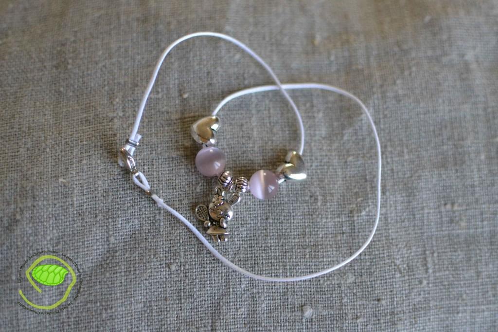 """Couleur argent avec des perles """"oeil de chat"""" roses, une cordelette blanche et un petit lapin"""