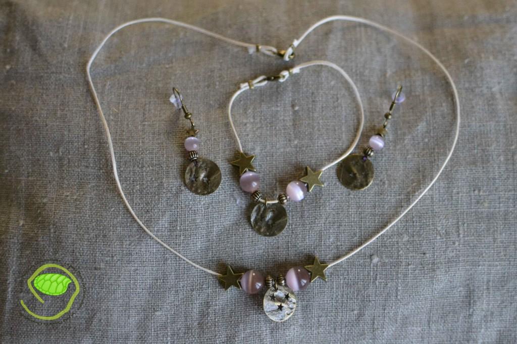 """Ensemble boucles d'oreilles, bracelet et collier avec des perles """"oeil de chat"""" roses, un cordon en cuir écru et les fameuses médailles à étoiles"""