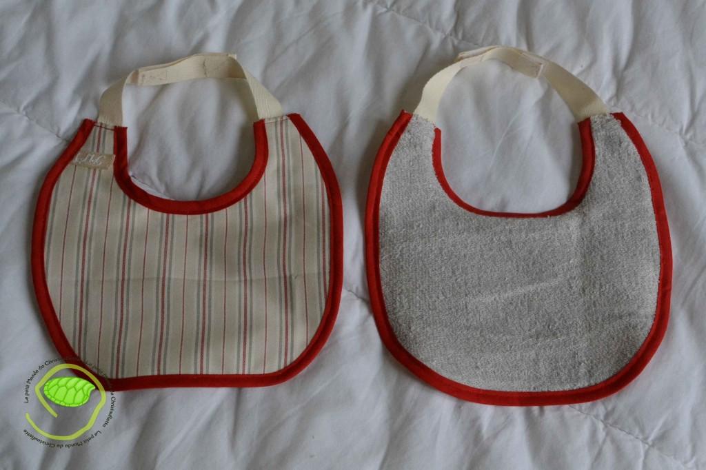2 bavoirs à scratch avec un biais rouge, un coton à rayures et de l'éponge grise L'un des deux est doublé par un tissu imperméable