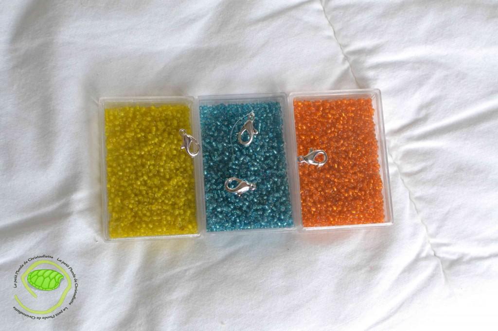 Des perles de rocailles jaunes, bleues et oranges ainsi que trois fermoirs argentés