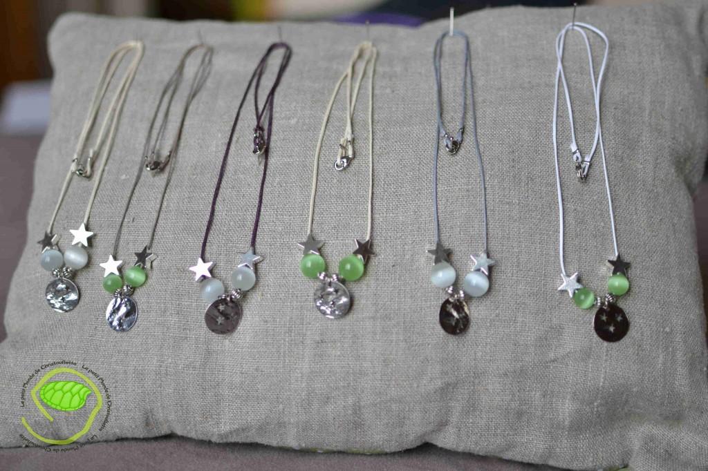 De couleur argent avec ma médaille avec des étoiles, des perles blanches ou vertes et une cordelette cuir de couleur différente