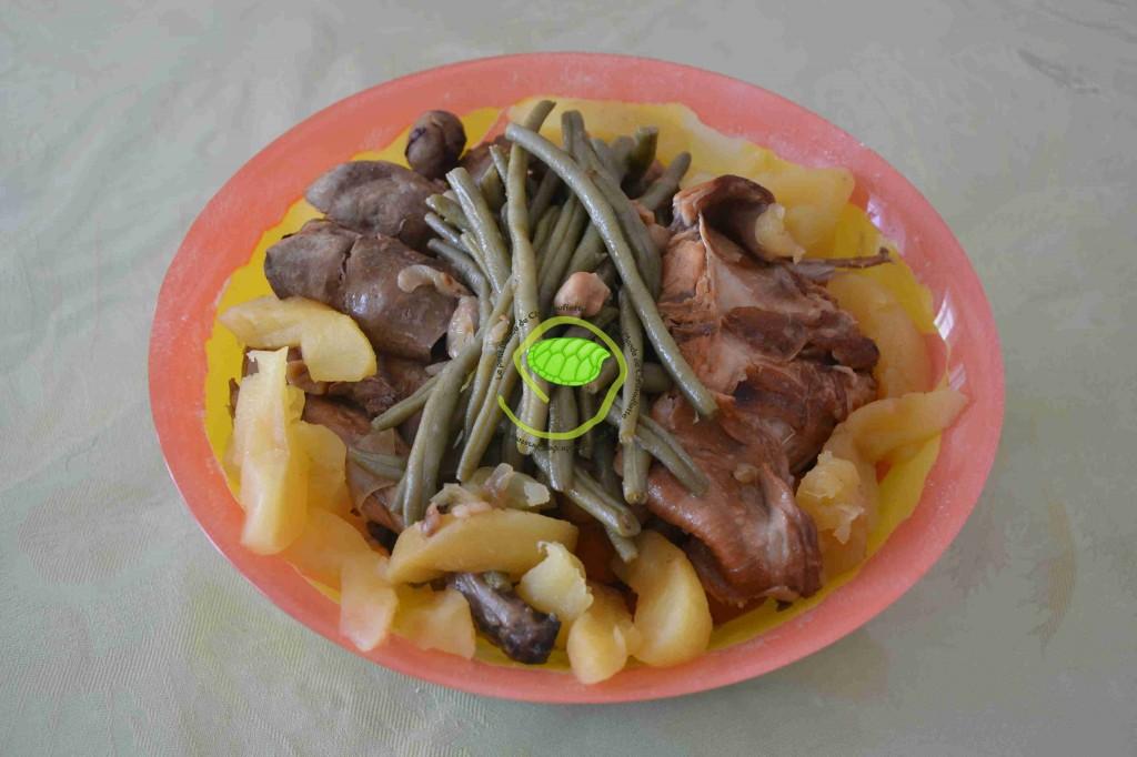 Un demi lapin avec les champignons de paris, les châtaignes, des carottes, des oignons, des pommes et des haricots
