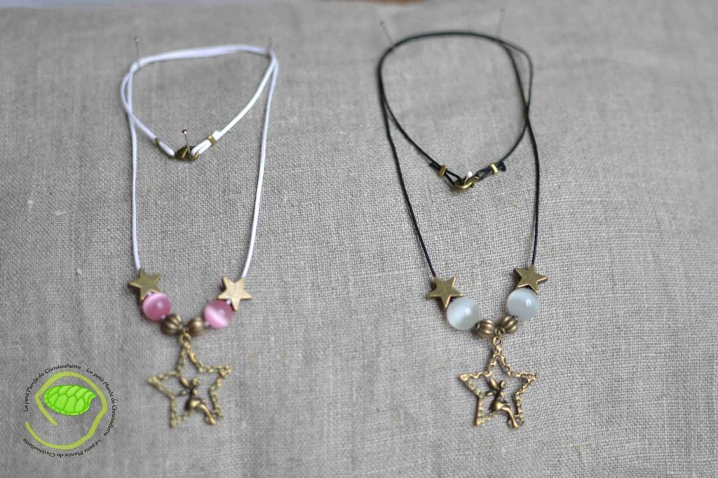 """De couleur bronze avec un pendentif fée ainsi que des étoiles, des perles """"oeil de chat"""" blanches et roses et une cordelette en cuir noire et blanche"""