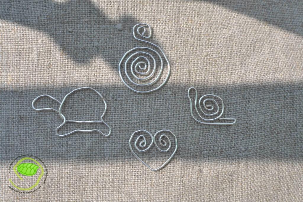 un escargot, un coeur, une tortue et une spirale en fils métallique argenté