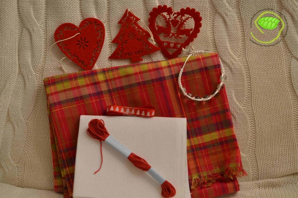 Trois pendouilles de Noël rouge, une écharpe en madras, un bracelet shamballa blanc, un carré de toile à broder, du fil rose et un ruban rouge.