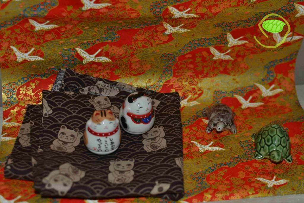 du papier, un coupon de tissu, deux tortues et deux maneki-neko